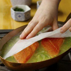 Coloque el papel pergamino para cocinar sobre el pescado mientras se cocina.
